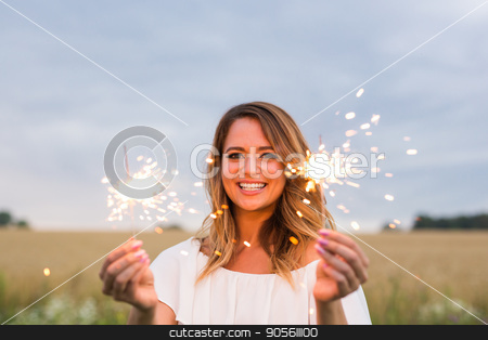 Outdoor photo of young beautiful happy smiling girl holding sparkler. Holidays concept stock photo, Outdoor photo of young beautiful happy smiling girl holding sparkler. Holidays concept by Satura86
