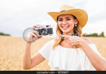 Woman holding retro camera stock photo, Woman holding retro camera in the field by Satura86