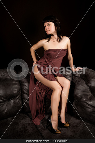 glamour woman in a brown dress leather sofa on a dark background stock photo, glamour woman in a brown dress leather sofa on a dark background. by Alexander