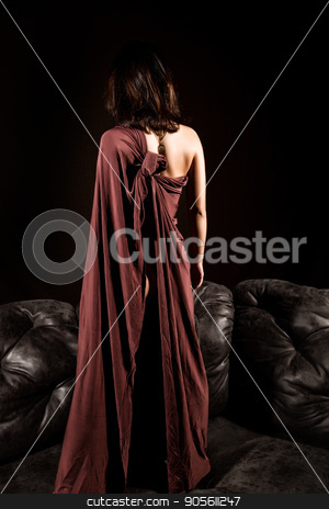 glamour woman in a brown cape stending on a leather sofa on a dark background. back view stock photo, glamour woman in a brown cape stending on a leather sofa on a dark background. back view. by Alexander
