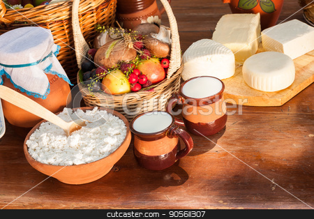 Dairy products on wooden table. Cheese and milk on the table in an earthenware dish. Rural food. Food background. stock photo, Dairy farm products on wooden table. Cheese and milk on the table in an earthenware dish. Rustic, organic food, farm products concept. Food background. by Dmitry