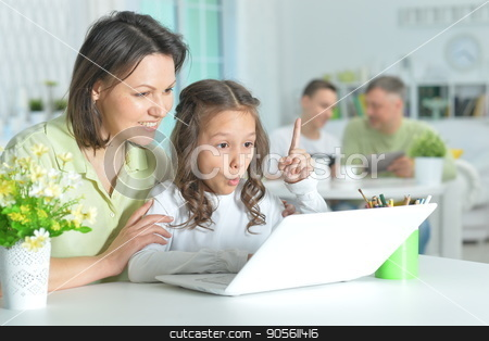 little girl and mother using laptop stock photo, Cute little girl and her mother sitting at table and using modern laptop by Ruslan Huzau