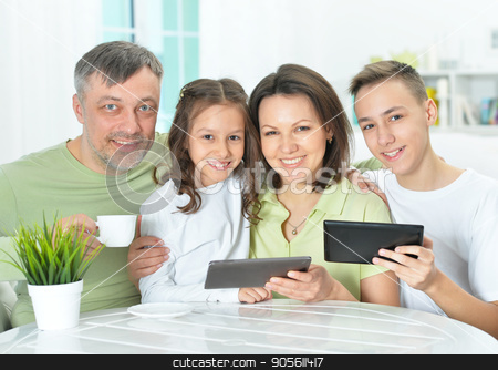 family sitting at table with gadgets stock photo, Happy family sitting at table with gadgets by Ruslan Huzau
