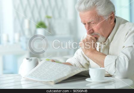 Elderly man reading a newspaper stock photo, Portrait of an elderly man reading a newspaper by Ruslan Huzau