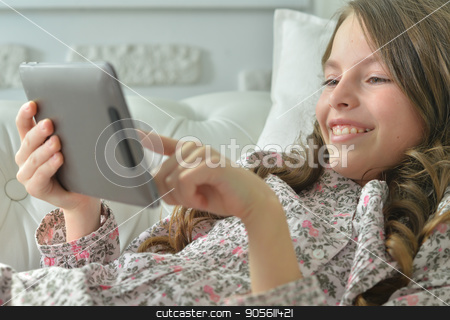 Little girl using tablet stock photo, Little girl in pajama using digital tablet by Ruslan Huzau