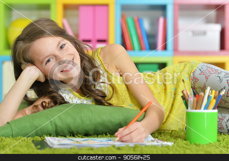 Little girl painting with pencil in her room  stock photo, Little girl painting with pencil in her room with bookshelves on background by Ruslan Huzau