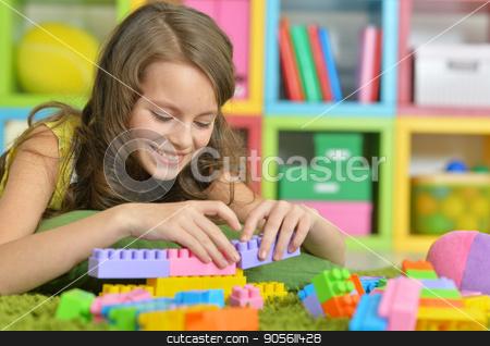 Cute girl playing with colorful plastic blocks  stock photo, Cute girl playing with colorful plastic blocks in room by Ruslan Huzau