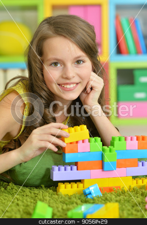 Cute girl playing with colorful plastic blocks  stock photo, Cute girl playing with colorful plastic blocks in room by Ruslan Huzau
