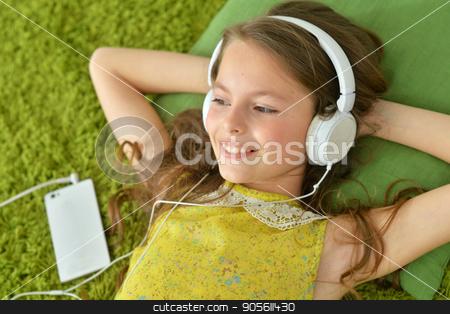 Cute little girl with headphones stock photo, Cute little girl with smartphone and headphones by Ruslan Huzau