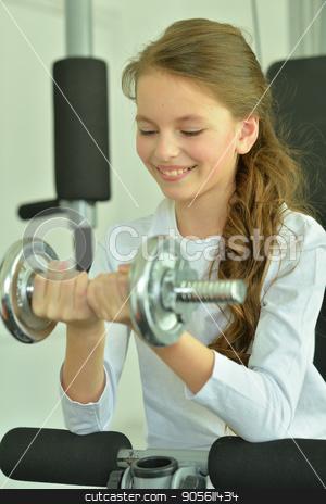 Little girl doing exercises  stock photo, Little girl doing exercises with dumbbell in gym by Ruslan Huzau