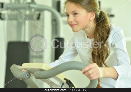 Little girl doing exercises stock photo, Little girl doing exercises in a gym by Ruslan Huzau