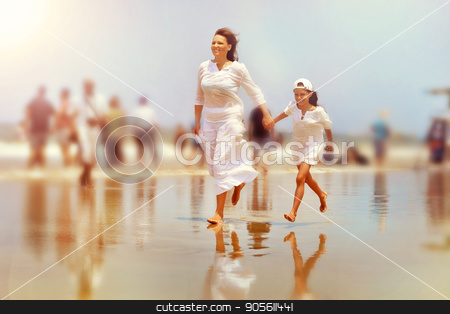 Mother with daughter running on beach stock photo, Mother with little daughter running on sandy beach by Ruslan Huzau