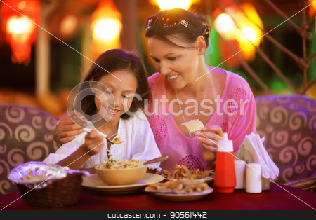Mother and daughter eating stock photo, Mother and daughter eating in a restaurant by Ruslan Huzau