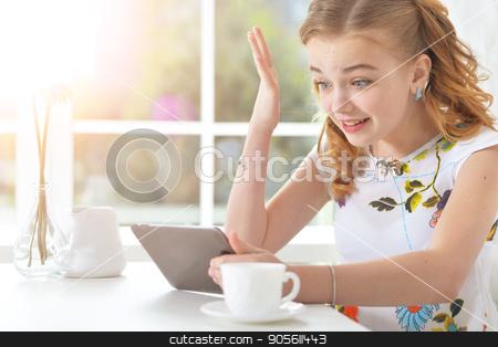 Surprised little girl looking at tablet stock photo, Surprised little girl sitting at table and looking at digital tablet by Ruslan Huzau