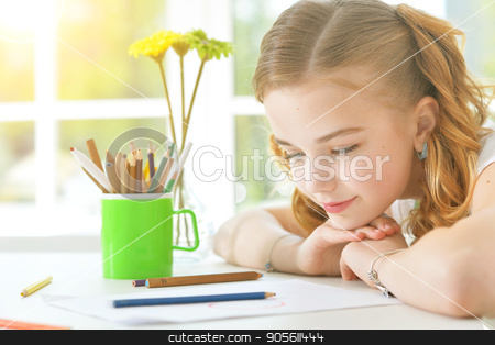 Little girl looking at drawings stock photo, Pretty little girl sitting at table and looking at paper with drawings by Ruslan Huzau