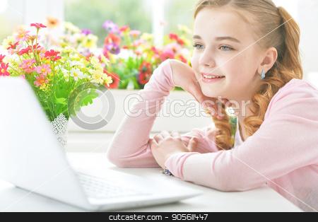 Little girl with modern laptop stock photo, Pretty little girl sitting at table with modern laptop by Ruslan Huzau