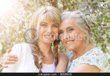 Beautiful young woman with mother stock photo, Family portrait of beautiful young woman with her mother near blooming tree by Ruslan Huzau