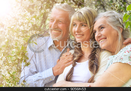 Parents with adult daughter stock photo, Family portrait of parents with adult daughter in spring trees by Ruslan Huzau