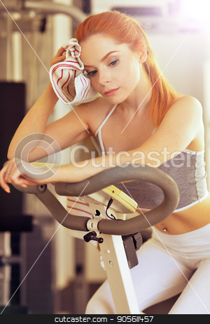 Young woman training in gym stock photo, Sporty young woman training in a gym by Ruslan Huzau