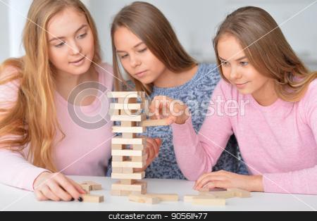 girls playing with wooden blocks stock photo, Three teenage girls playing with wooden blocks by Ruslan Huzau