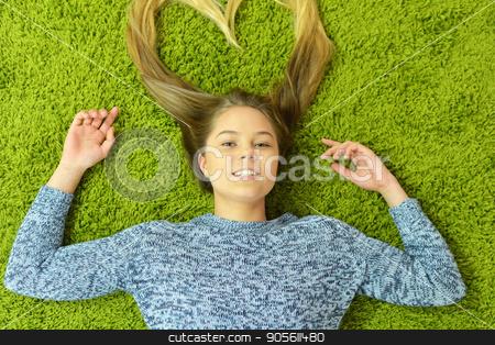 Teen girl lies on the carpet stock photo, Pretty teen girl lies on the carpet by Ruslan Huzau