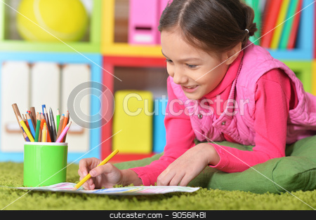 Cute little girl drawing picture stock photo, Cute little girl lying on floor and drawing picture by Ruslan Huzau