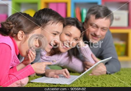 Big family lying on floor  stock photo, Big happy family lying on floor in front of laptop by Ruslan Huzau