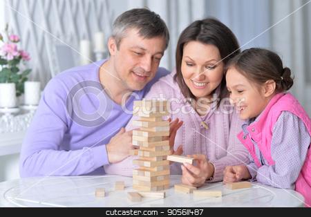 Happy family sitting playing  stock photo, Happy family sitting at table and playing with wooden blocks by Ruslan Huzau