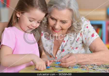 Grandmother collecting puzzle stock photo, Portrait of a grandmother collecting puzzle with her granddaughter by Ruslan Huzau