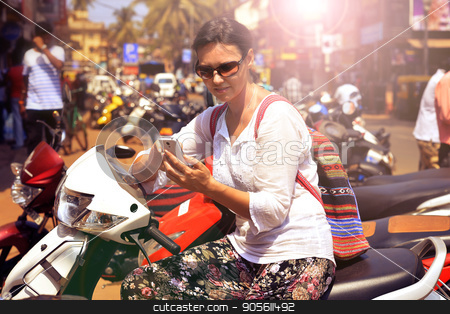 Woman in sunglasses sitting on motorcycle stock photo, Woman in sunglasses sitting on motorcycle and looking in smartphone by Ruslan Huzau
