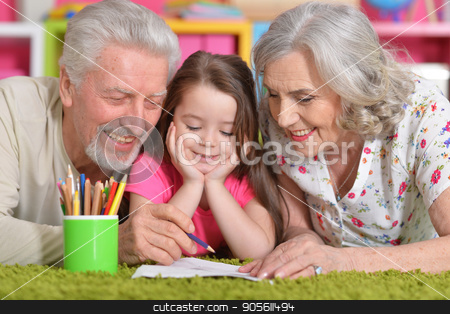 Grandparents playing with grandaughter stock photo, Grandparents playing with their grandaughter while lying on floor by Ruslan Huzau