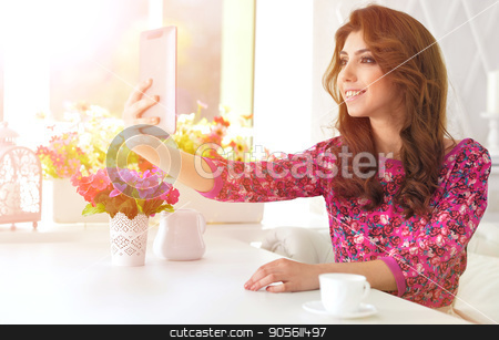 Beautiful young woman with digital tablet  stock photo, Beautiful curly young woman sitting at kitchen table with digital tablet by Ruslan Huzau