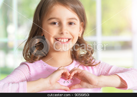Girl holding hands in shape of heart stock photo, Cute little girl holding hands in shape of heart by Ruslan Huzau