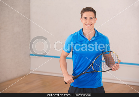 Young man squash player exercise game in the gym stock photo, Young brunette man standing in the gym squash game play by Dmytro Sidelnikov