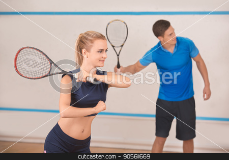 Young man and woman play squash in the gym stock photo, Young man and woman squash players together game by Dmytro Sidelnikov