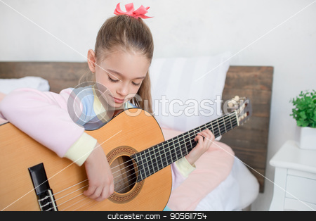 Young teenager girl alone at home childhood stock photo, Young teenager girl alone at home childhood playing guitar by Dmytro Sidelnikov