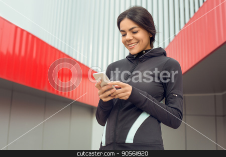Young woman active exercise workout on street outdoor stock photo, Young femaleactive exercise workout on street outside using smartphone by Dmytro Sidelnikov