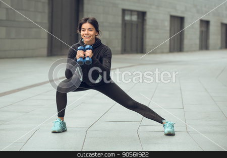 Young woman active exercise workout on street outdoor stock photo, Young femaleactive exercise workout on street outside with dumbbells by Dmytro Sidelnikov