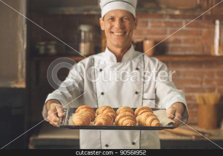 Bakery chef cooking bake in the kitchen professional stock photo, Bakery chef cooking bake in the kitchen professional holding croissants by Dmytro Sidelnikov