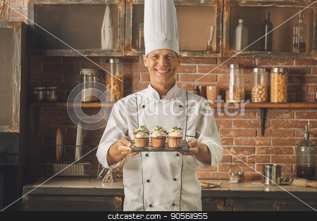 Bakery chef cooking bake in the kitchen professional stock photo, Bakery chef cooking bake in the kitchen professional holding cakes by Dmytro Sidelnikov