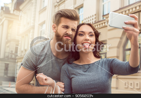 Young couple tourists city walk together vacation stock photo, Young couple woman and man tourists city walk together vacation taking pictures by Dmytro Sidelnikov