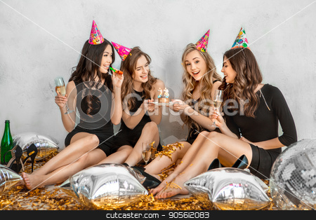 Young women together celebrating birthday isolated on white stock photo, Young female friends together celebration white background cake by Dmytro Sidelnikov