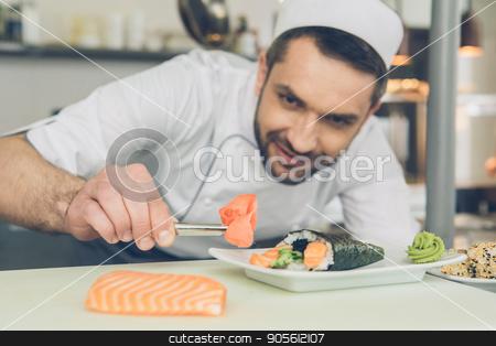Man japanese restaurant chef cooking in the kitchen stock photo, Male japanese restaurant chef cooking in the kitchen adding ingredients by Dmytro Sidelnikov