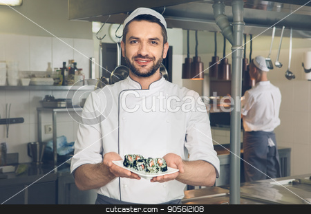 Man japanese restaurant chef cooking in the kitchen stock photo, Male japanese restaurant chef cooking in the kitchen dish cooked by Dmytro Sidelnikov