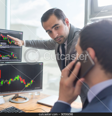 Stock brokers looking at computer screens, trading online. stock photo, Businessmen trading stocks online. Stock brokers looking at graphs, indexes and numbers on multiple computer screens. Colleagues in discussion in traders office. Business success concept. by kasto