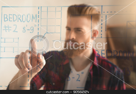 Young man architect working in the office ocuupation stock photo, Young male architect working indoors planning draft by Dmytro Sidelnikov