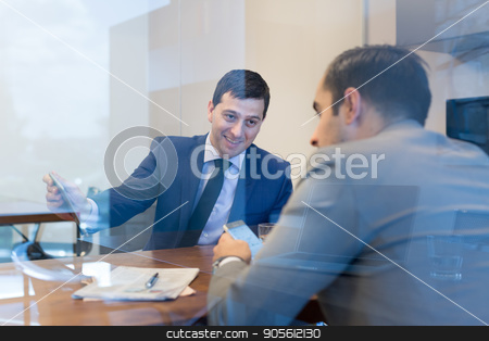 Two young businessmen using smart phones and touchpad at meeting. stock photo, Image of two young businessmen using smart phones and touchpad at meeting in moder office. by kasto