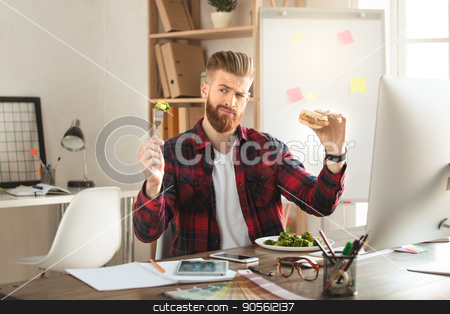 Young man architect working in the office ocuupation stock photo, Young male architect working indoors eating lunch by Dmytro Sidelnikov