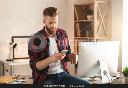 Young man architect working in the office ocuupation stock photo, Young male architect working indoors using digital device by Dmytro Sidelnikov