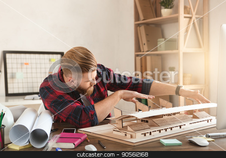 Young man architect working in the office ocuupation stock photo, Young male architect working indoors model construction by Dmytro Sidelnikov